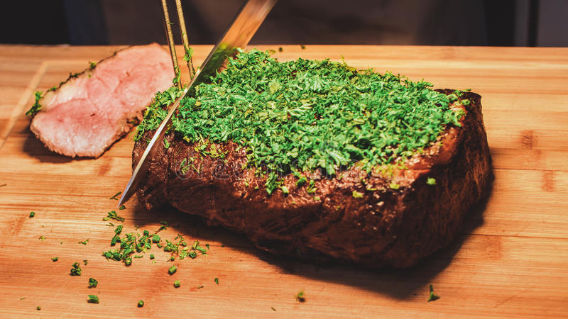 Chef is cutting steak royalty free stock image