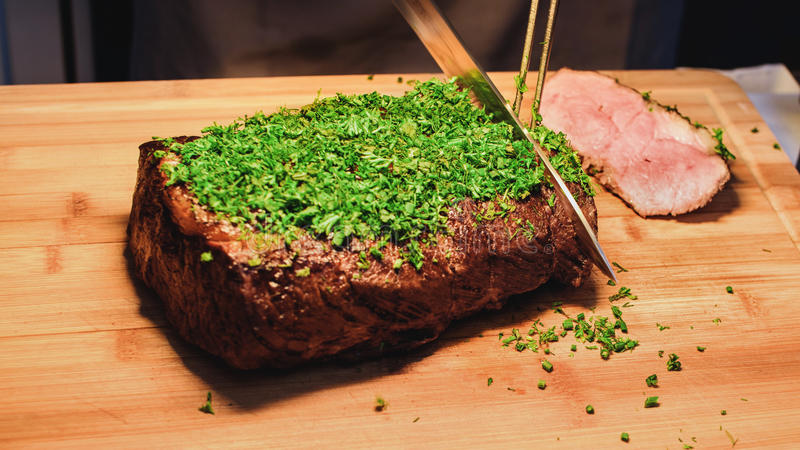 Chef is cutting steak stock image