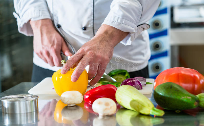 Chef cutting vegetables in his restaurant kitchen royalty free stock photo