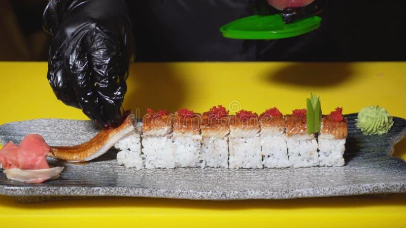 Chef décorant des petits pains de sushi pour servir dans le restaurant Vue Le plan rapproché du chef professionnel met la poignée photographie stock libre de droits