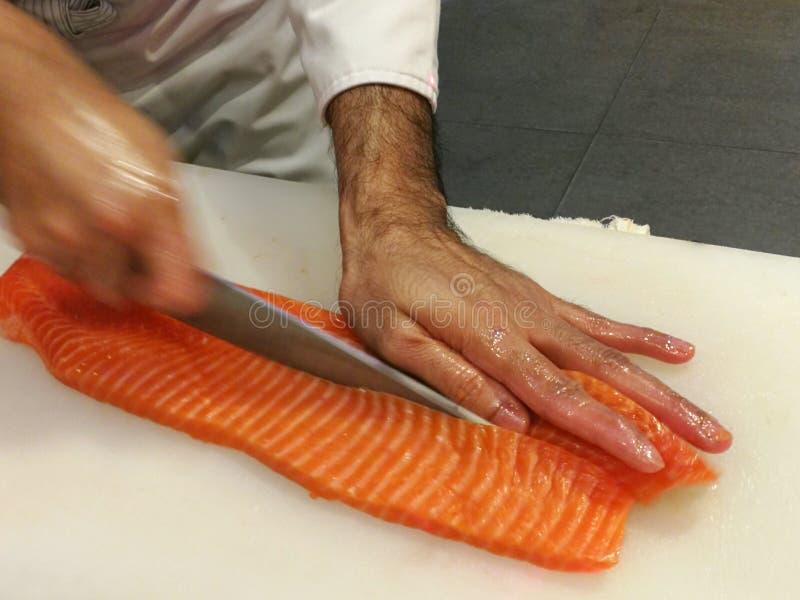 Chef découpant un filet en tranches saumoné frais cru avec un couteau pointu sur une planche à découper blanche photographie stock libre de droits