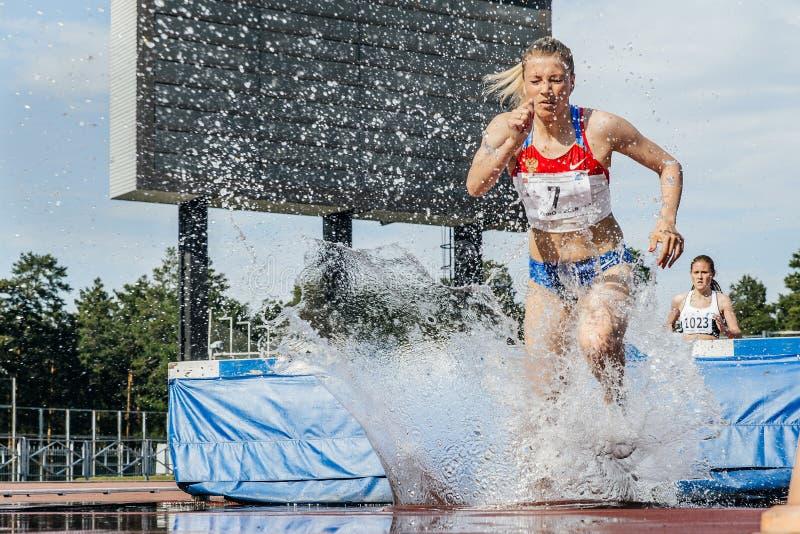 Chef d'athlètes féminins de course à la course d'obstacles image stock