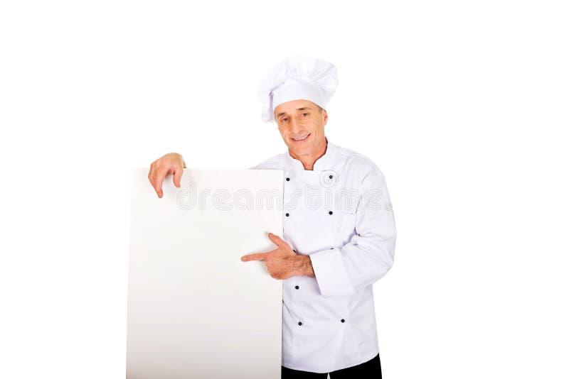 Chef dans l'uniforme blanc tenant la bannière vide images stock