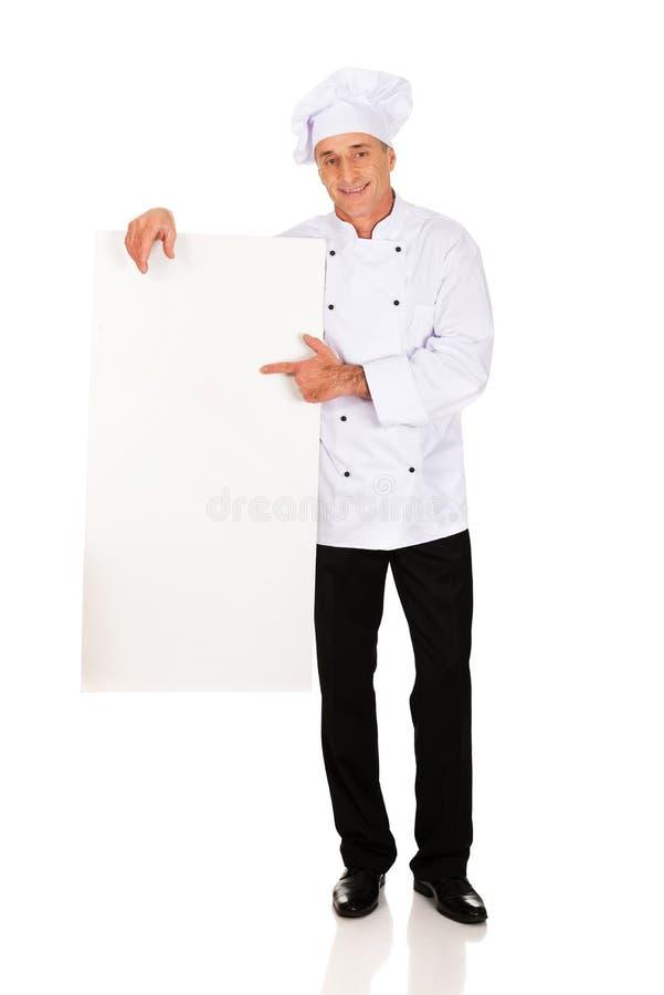 Chef dans l'uniforme blanc tenant la bannière vide photos libres de droits