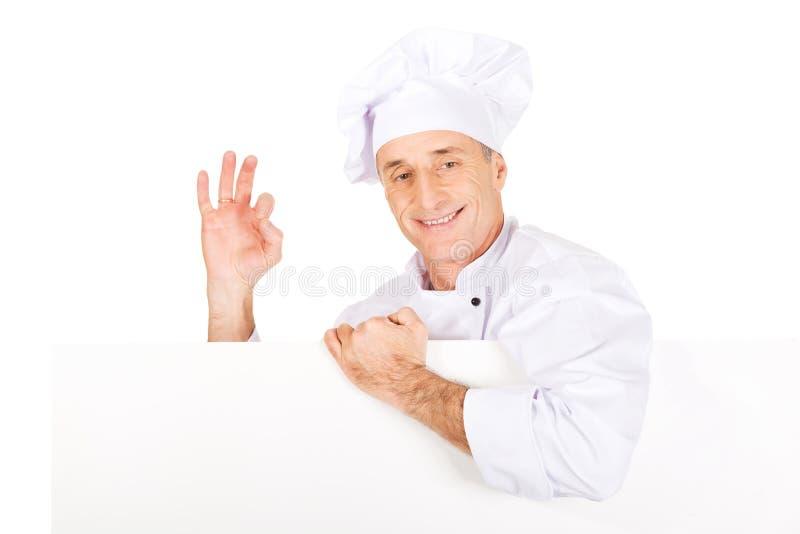 Chef dans l'uniforme blanc tenant la bannière vide photographie stock