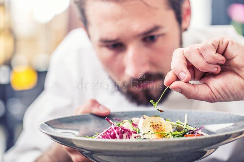 Chef dans la cuisine d'hôtel ou de restaurant préparant la nourriture photo stock