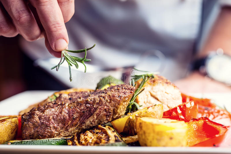 Chef dans la cuisine d'hôtel ou de restaurant faisant cuire seulement des mains Bifteck de boeuf préparé avec la décoration végét photos stock