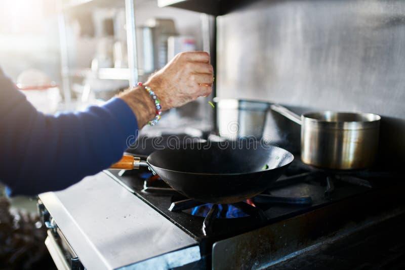 Chef dans la cuisson de nourriture d'assaisonnement de cuisine de restaurant photos libres de droits
