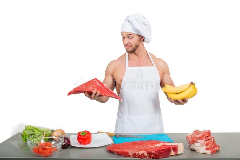 Chef dans un tablier blanc tenant la viande et des bananes photos libres de droits