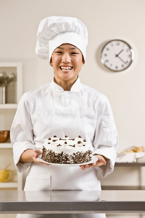 Chef de boulangerie dans des blancs de toque et de chefs image stock