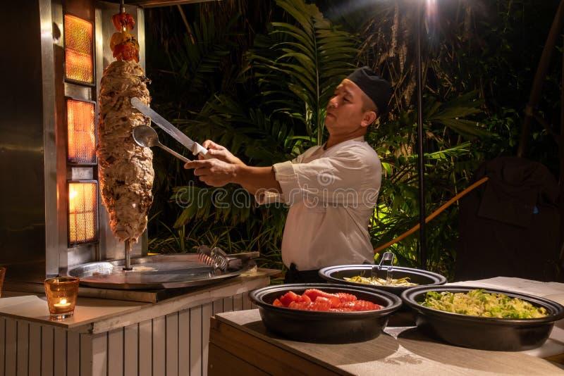 Chef de cuisine faisant cuire le shawarma pendant le dîner international de cuisine dehors installé au restaurant d'île image stock