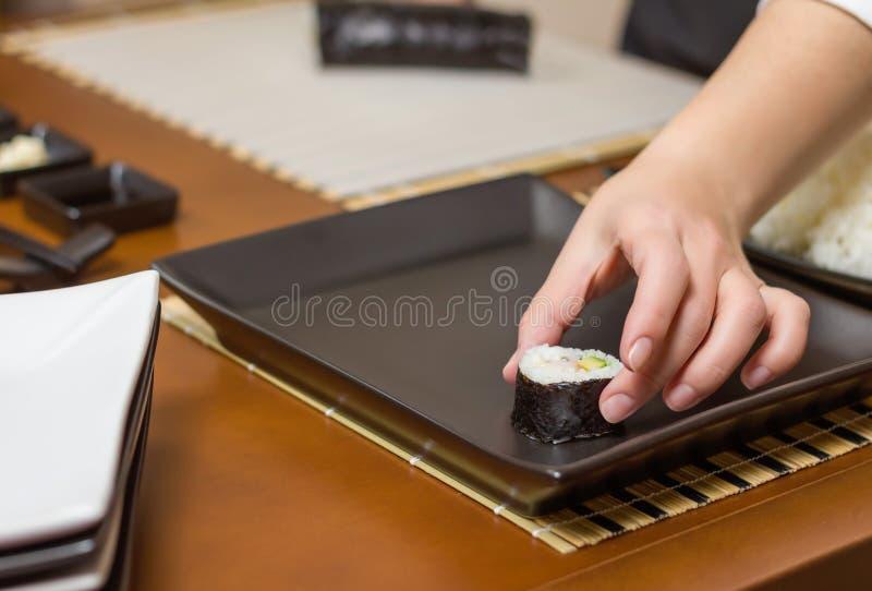 Chef de femme plaçant les petits pains de sushi japonais sur un plateau photographie stock