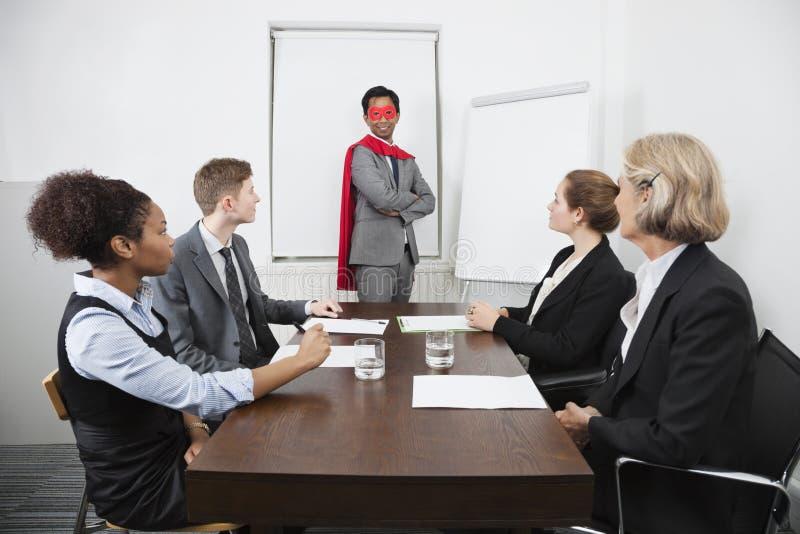 Chef de file des affaires comme super héros devant des collègues lors de la réunion dans la salle de conférence photographie stock libre de droits