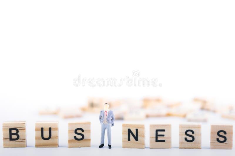 Chef de file des affaires Concept Petit chiffre de personnes miniatures se tenant dans le cube en bois moyen avec des affaires de photo libre de droits