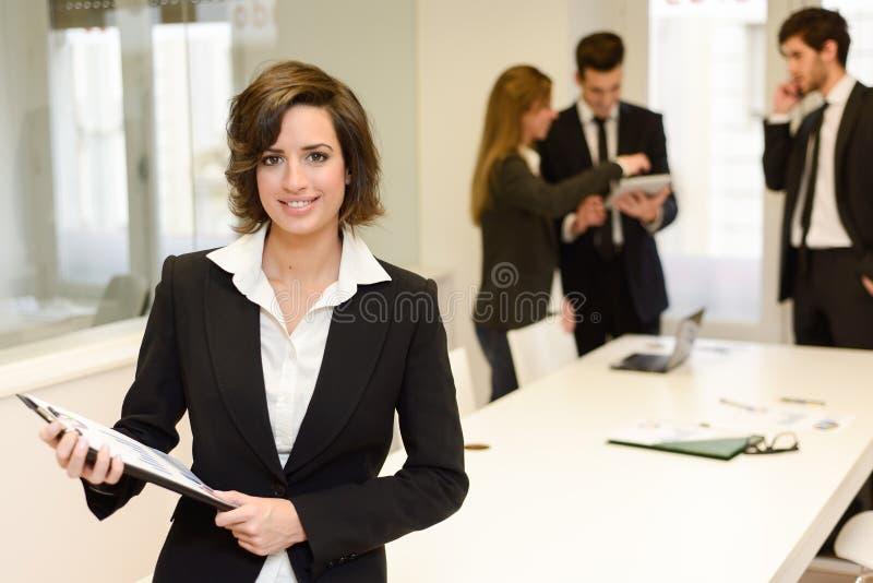 Chef de file des affaires regardant l'appareil-photo dans l'environnement de travail photographie stock libre de droits
