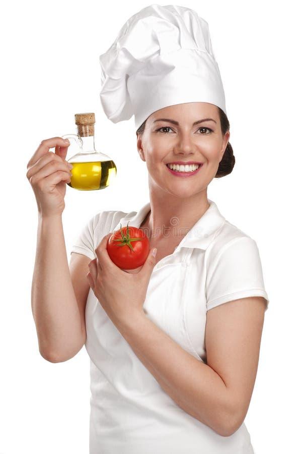 Chef de jeune femme montrant des ingrédients pour la nourriture italienne image libre de droits