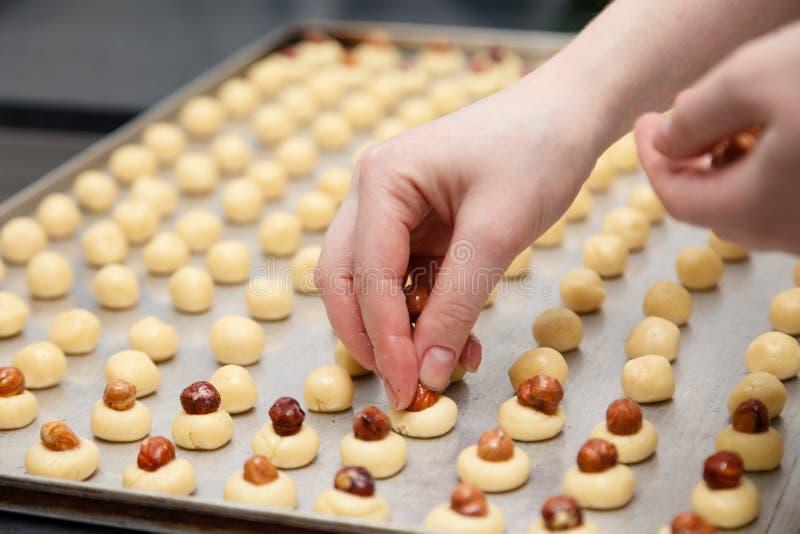 Chef de pâtisserie de plan rapproché à la cuisine professionnelle du restaurant transformant les biscuits sablés, coupant la pâte image stock