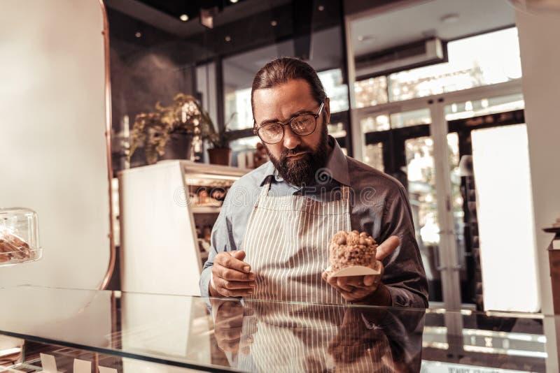 Chef de repostería profesional agradable que sostiene una torta foto de archivo libre de regalías