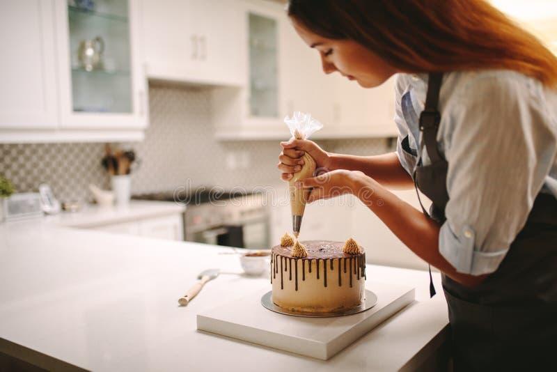 Chef de repostería que adorna la torta de chocolate foto de archivo libre de regalías