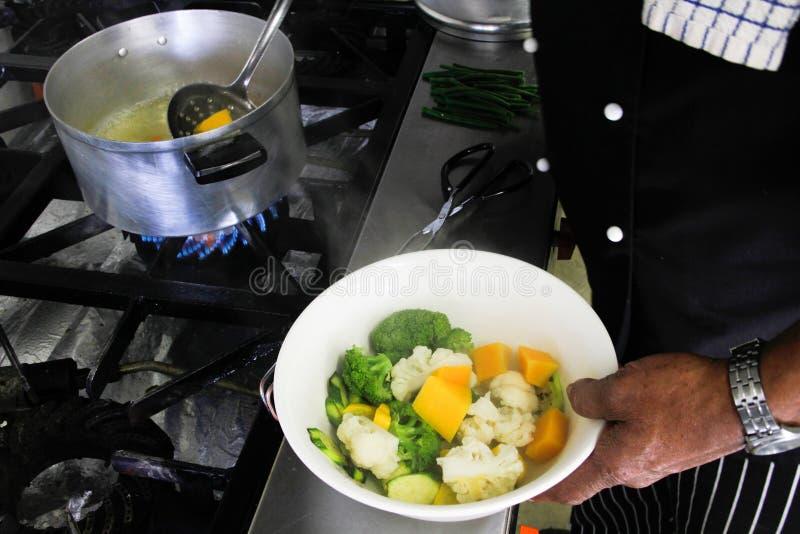Chef de restaurant bombant vers le haut les légumes frais image libre de droits