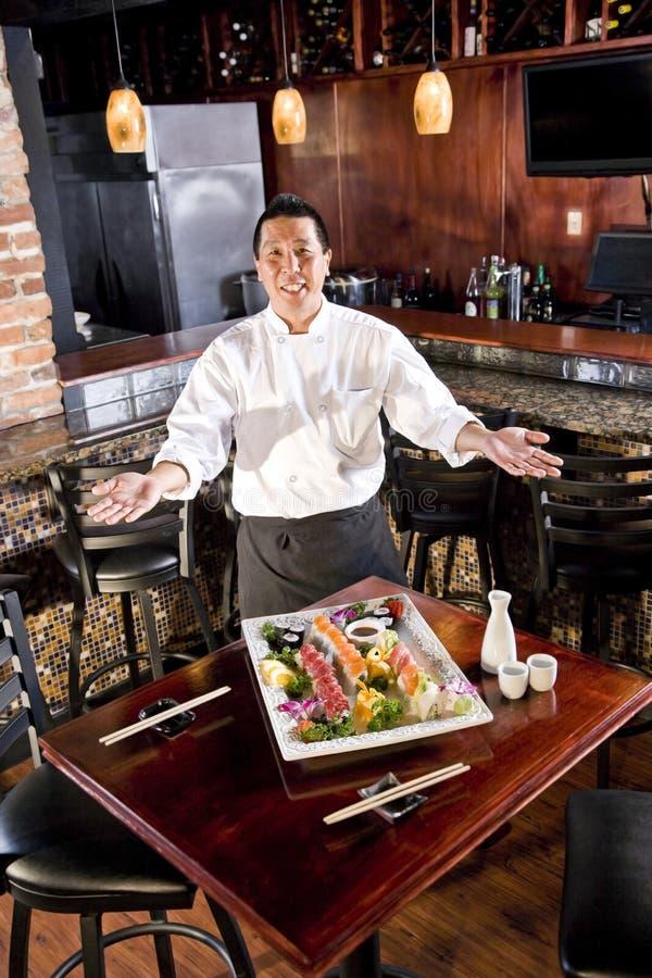 Chef de restaurant japonais présent le champ de cablage à couches multiples de sushi photographie stock
