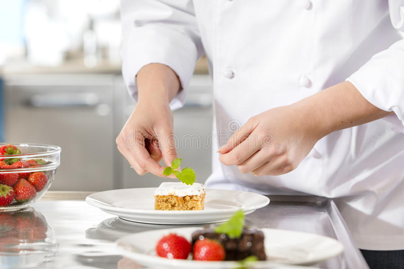 Chef decorate dessert cake with lemon leaf. Close-up of a professional female chef who decorates dessert cake with strawberry and lemon leaf. Large industry stock photography