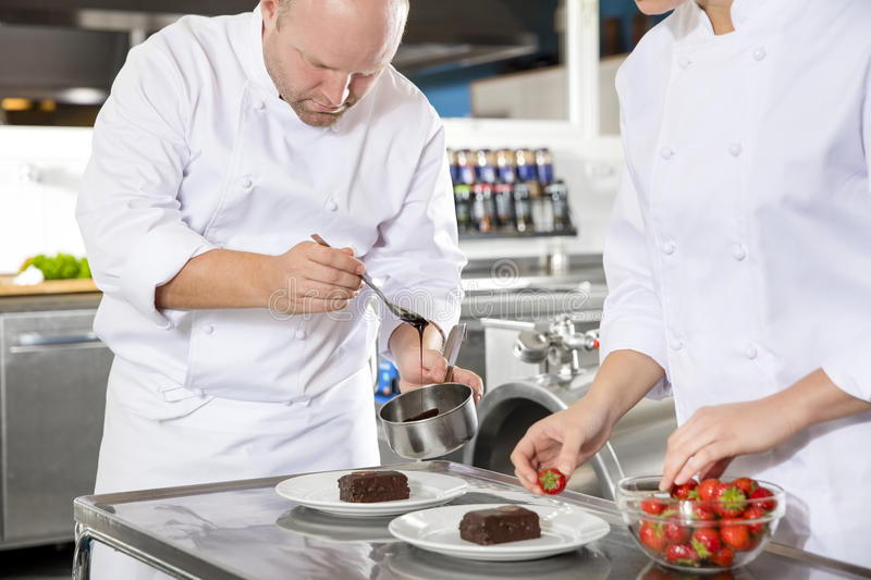 Chef decorates dessert cake with chocolate sauce in kitchen. Close-up of professional chefs who decorates dessert cake with strawberry and chocolate sauce. Large stock images