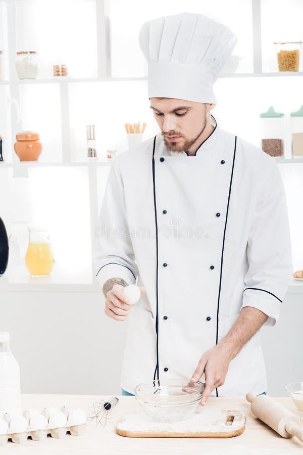 Chef in den einheitlichen breakseggs in der Schüssel, zum des Teigs in der Küche zuzubereiten lizenzfreie stockfotos