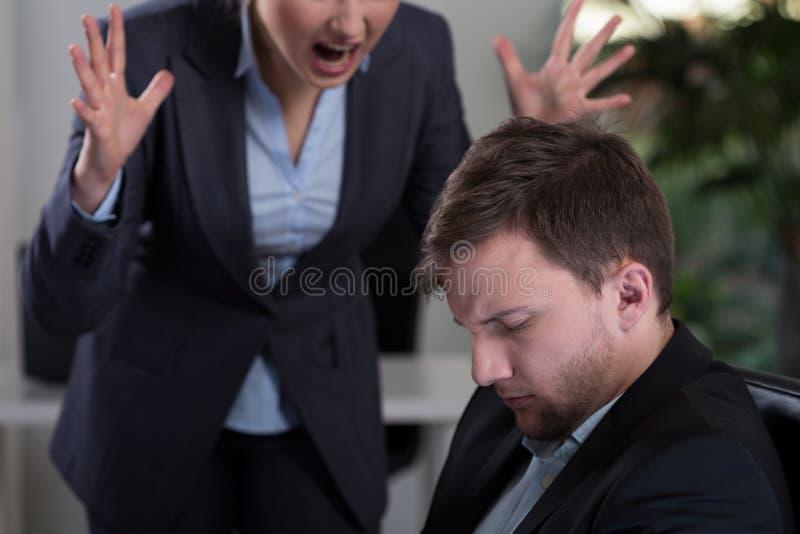 Chef, der am Angestellten schreit stockfotografie