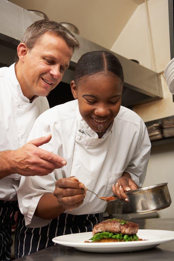 Chef, der Auszubildenden in der Gaststätte-Küche anweist lizenzfreie stockbilder