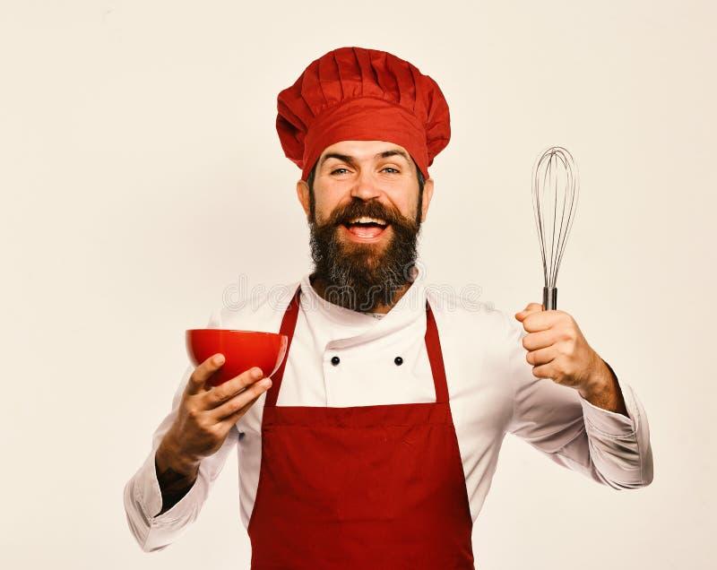Chef, der Bestandteile in der roten Platte mischt oder peitscht stockbild