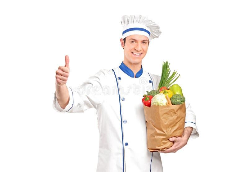 Chef, der Daumen aufgibt und einen Lebensmittelgeschäftbeutel anhält stockfoto