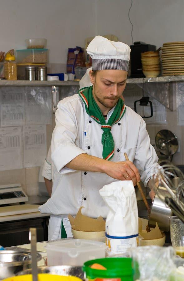 Chef, der an der Küche kocht stockbild