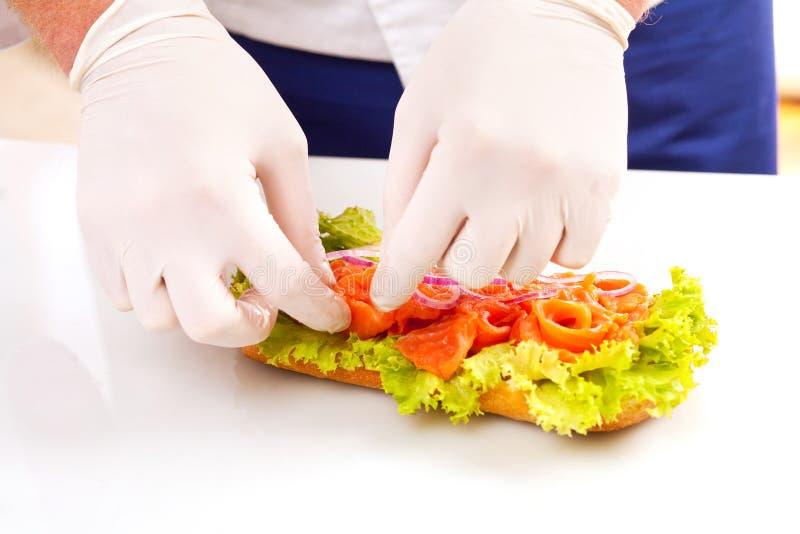 Chef, der Sandwiche macht lizenzfreie stockfotografie