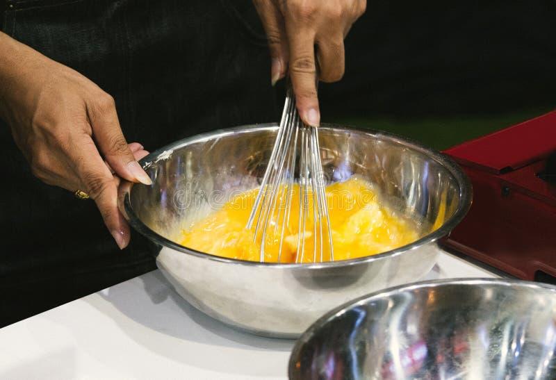 Chef, der Eier in der Schüssel auf Küchentisch wischt lizenzfreies stockbild