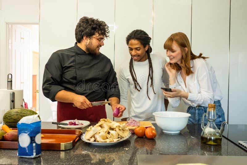 Chef, der ein junges Paar der unterschiedlichen Zucht unterrichtet, wie man kocht stockfoto