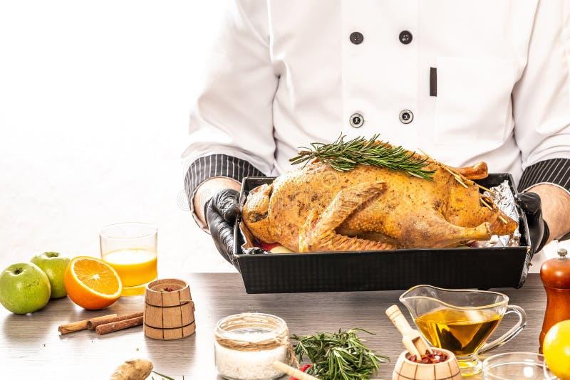 Chef, der eine festliche Ente für das Weihnachten, Silvesteressen kocht Die frische Ente vorbereiten angefüllt mit Äpfeln Platz f stockfotografie