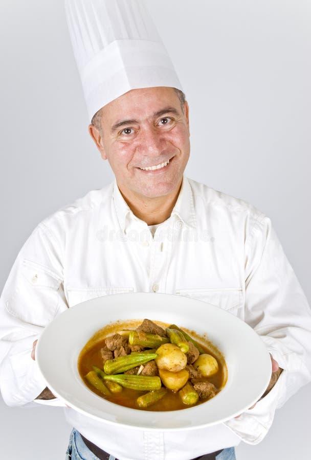 Chef, der eine Platte des Rindfleisch-Eintopfgerichts anhält stockfotografie