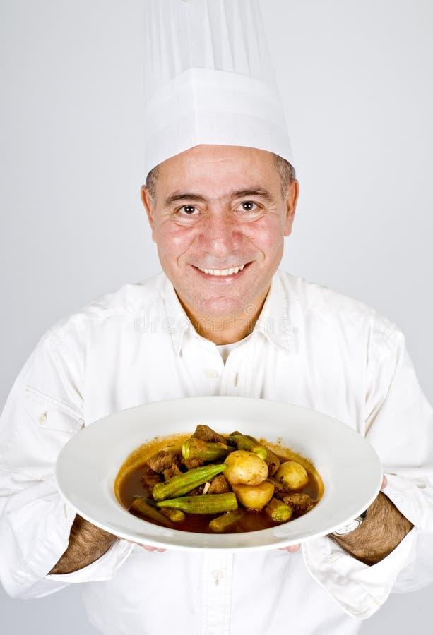 Chef, der eine Platte des Rindfleisch-Eintopfgerichts anhält stockbild