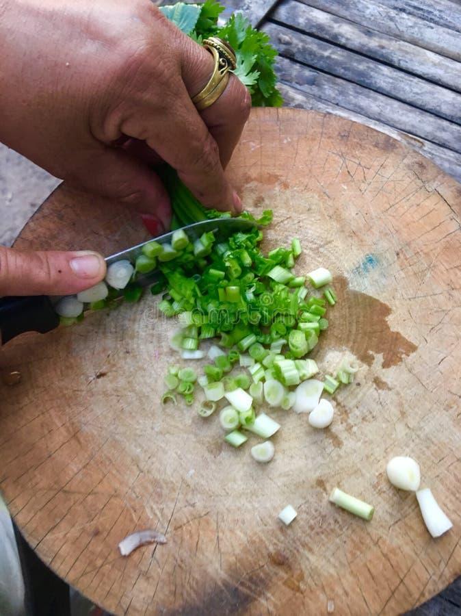 Chef, der Frühlingszwiebel durch Messer mit der Hand auf dem hölzernen Brett hackt lizenzfreie stockfotografie