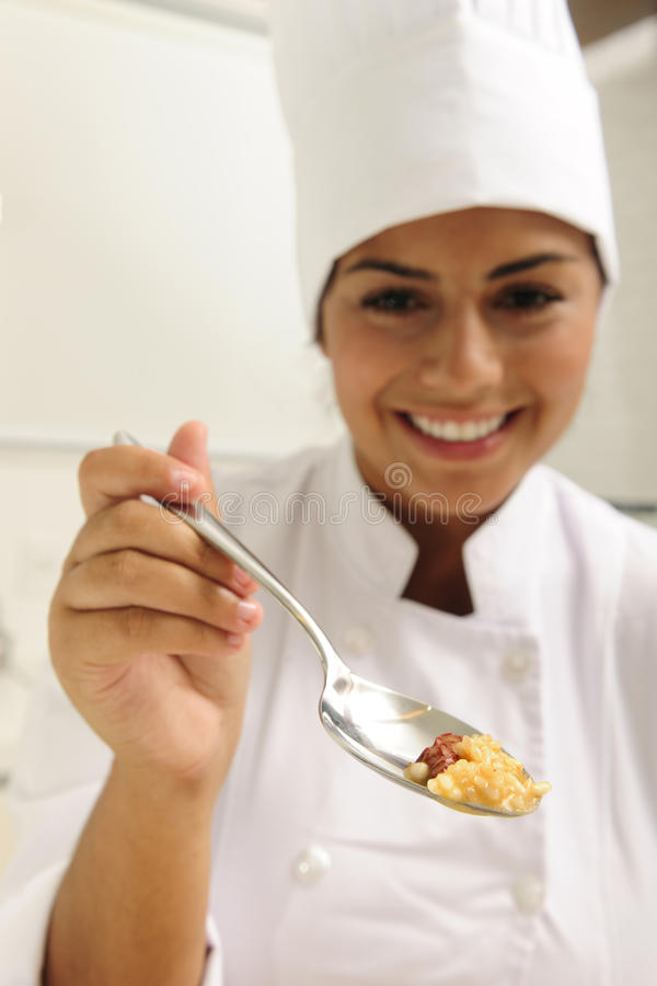 Chef, der geschmackvollen Risotto auf Löffel für Probieren anbietet stockbild