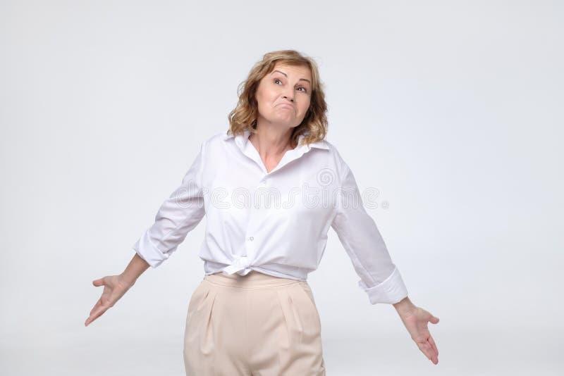 Chef der hübschen reifen Frau im Ruhestand, der verwirrtes Achselzucken ihre Schultern schaut lizenzfreies stockbild