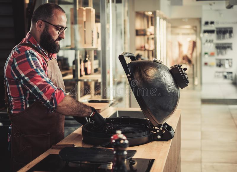 Chef, der Holzkohlen bevor dem Grillen in einem Restaurant vorbereitet stockfotos
