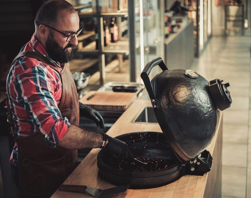 Chef, der Holzkohlen bevor dem Grillen in einem Restaurant vorbereitet lizenzfreies stockbild