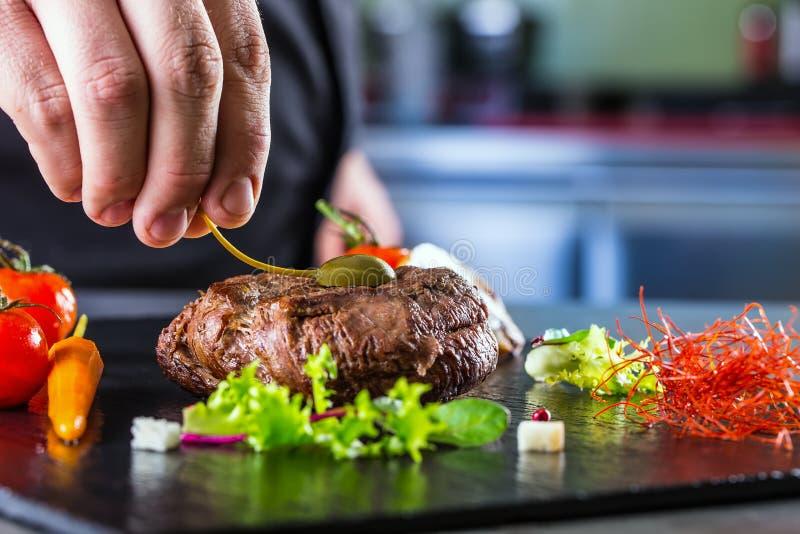 Chef in der Hotel- oder Restaurantküche kochend, nur Hände Zugebereitetes Rindfleischsteak mit Gemüsedekoration stockfotografie