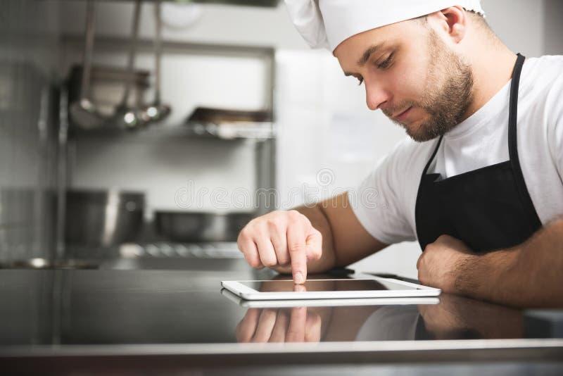 Chef in der Küche unter Verwendung der Tablette stockfotografie