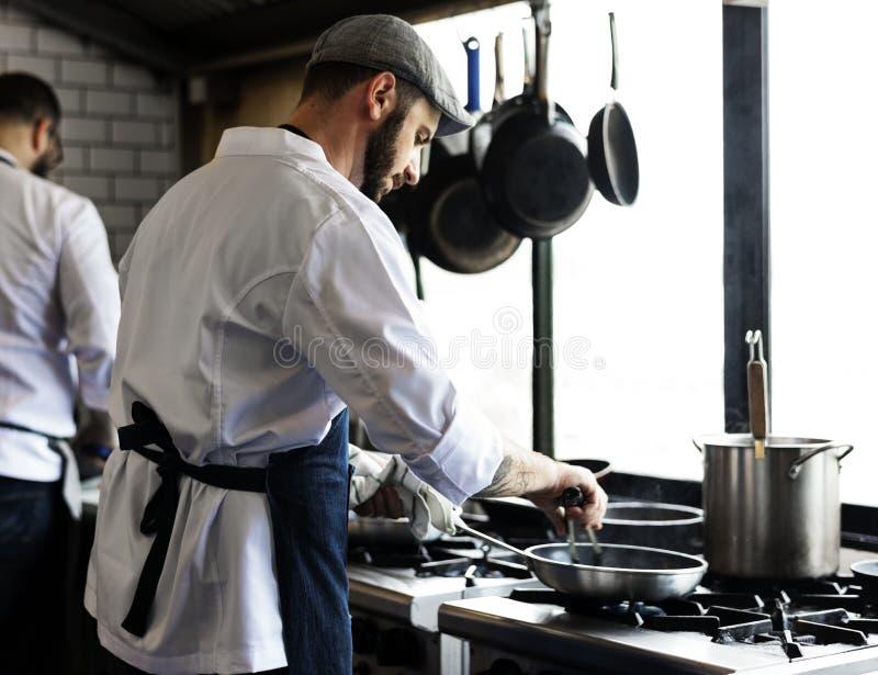 Chef, der Lebensmittel in der Restaurantküche kocht stockfotos