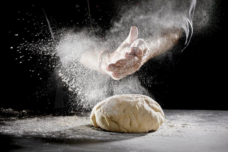 Chef, der Mehl beim Kneten des Teigs zerstreut lizenzfreies stockbild