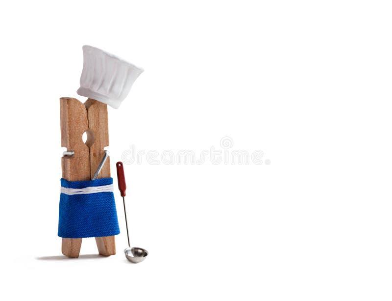 Chef, der mit Küchenlöffel, Suppenschöpflöffel kocht Lustiger Wäscheklammerrestaurantcharakter kleidete im Hut, blaues Schutzblec lizenzfreies stockbild