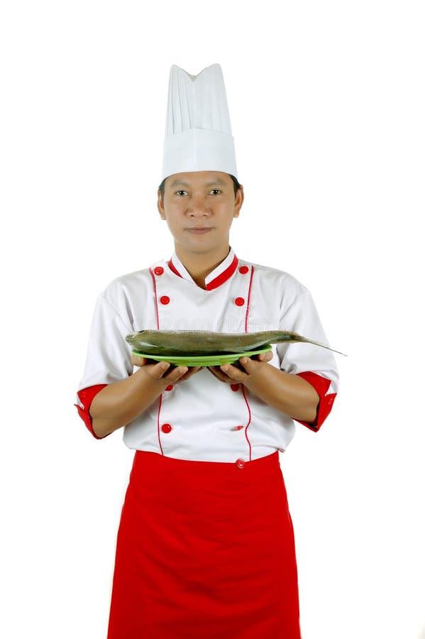 Chef, der rohe Fische auf einer grünen Platte anhält stockfotos